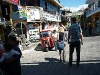 A small street in Guatemala full of signs in English. How does this affect a sustainable development?